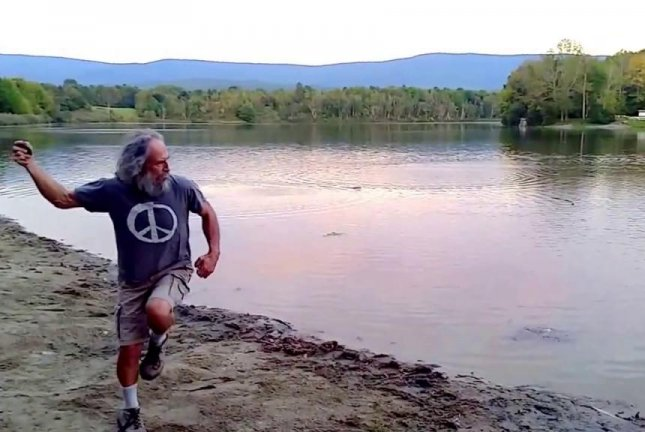Professional stone skipper Kurt Steiner winds up for a throw that makes it all the way across Lake Paran. Stone Skipper/YouTube video screenshot