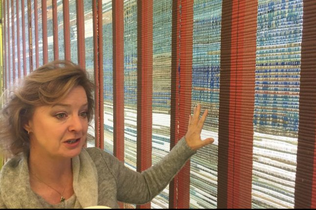 Marianna Trevino-Wright, executive director of the National Butterfly Center near McAllen, Texas, explains an art installation designed to show what the 18-foot-high border wall will look like. Photo by Patrick Timmons/UPI