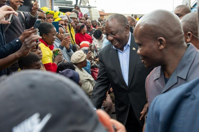 South African President Cyril Ramaphosa greets supporters before he votes in the country's national elections. The ruling ANC party retained power with 57 percent of the vote. Photo by Yeshiel Panchia