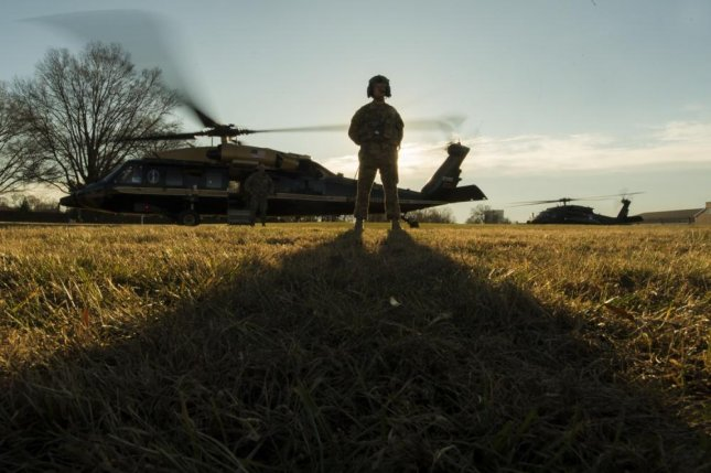 A U.S. Army aircrewman stands near a VH-60N White Hawk helicopter before departing Joint Base Myer-Henderson Hall, Virginia, in December 2017. The U.S. Navy is in the process of replacing its presidential helicopter fleet with VH-60N aircraft. Photo by Dominique A. Pineiro/U.S. Navy