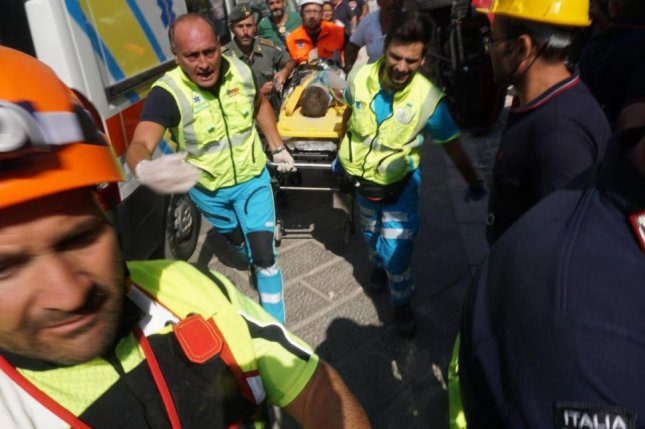 A child is rescued after a 4.0-magnitude earthquake struck the Italian resort island of Ischia late Monday. Two people were killed. Photo by ANSA/EPA