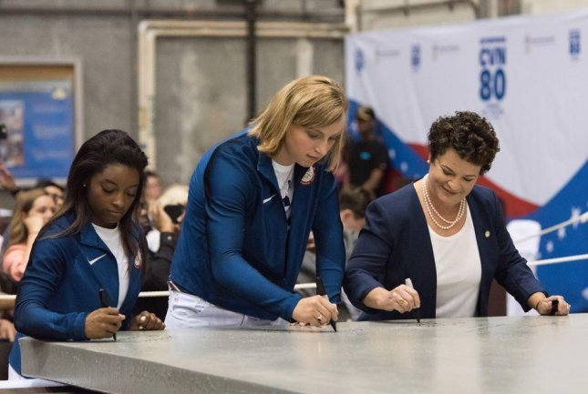 Olympic Gold Medalists and ship sponsors Simone Biles (left) and Katie Ledecky (center) sign a piece of steel for a new Gerald R. Ford-class aircraft carrier. On right is Newport News Shipbuilding President Jennifer Boykin. Photo Courtesy Matt Hildreth/HII