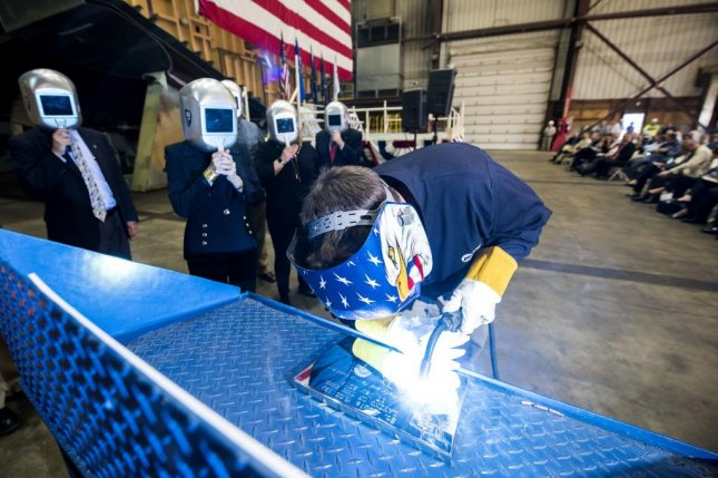 A welder authenticates the keel of LCS 19, the future USS St. Louis, by welding the initials of ship sponsor Barbara Broadhurst Taylor. The Keel Laying is the formal recognition of the start of the ship's module construction process. Photo courtesy Lockheed Martin