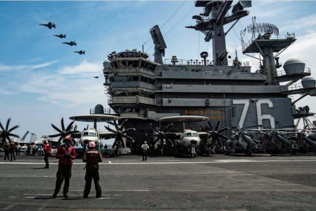 Crewmen aboard the aircraft carrier USS Ronald Reagan watch fighter planes in formation as the U.S. Navy and Air Force staged a joint exercise this week off the Japanese coast. Photo courtesy of U.S. 7th Fleet
