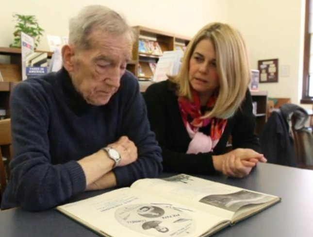 Former Bound Brook mayor Frank Ryan, 84, (L) returned an overdue library book from 1944 after his daughter Karen (R) found it in a barrel in his attic. The book was returned in a ceremony attended by about 30 people and was placed in the library's archive.  Screen capture/mycentraljersey.com