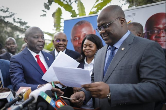 Congo opposition leader Felix Tshisekedi (R) exchanges documents with Vital Kamerhe, the leader of the Union for the Congolese Nation, on November 23. Photo by Dai Kurokawa/EPA-EFE