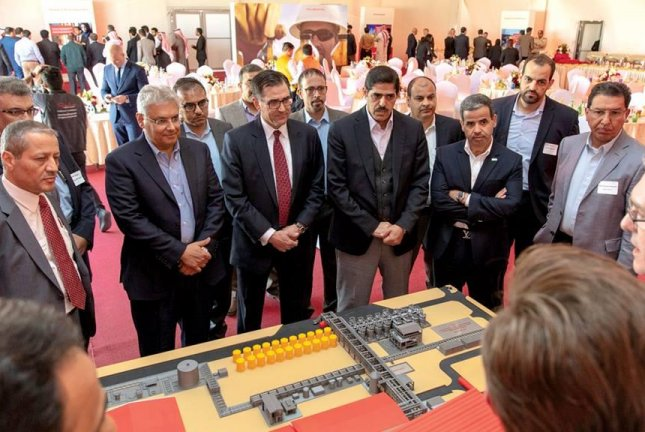 Mohammed Y. Al Qahtani, Saudi Aramco senior vice president of Upstream, second from left in a blue shirt, and Jeff Miller, Halliburton president and CEO, fourth from the left in a red tie, look at a model of the new plant. Photo courtesy of Saudi Aramco