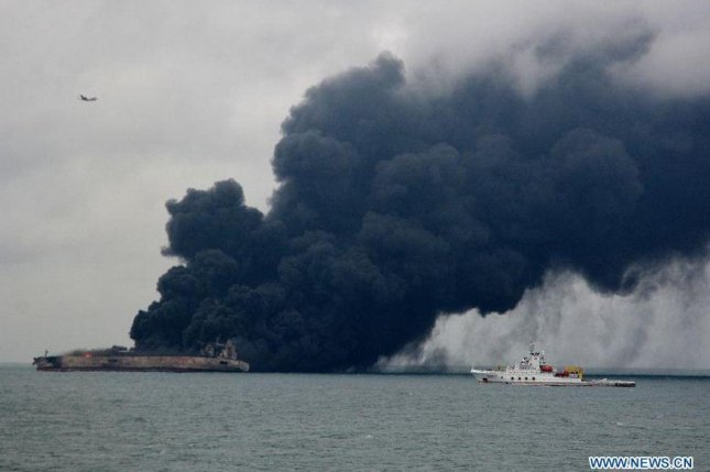 The Iranian oil tanker that crashed with a Chinese freighter carrying grain from the United States is seen listing and billowing thick black smoke during the weekend in an image from China's official Xinhua News Agency.