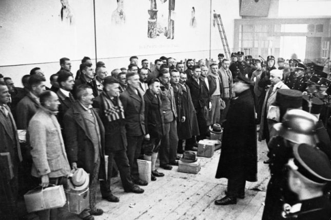 Dachau camp commander Theodor Eicke speaks to prisoners prior to their release. Dachau was originally created to hold political opponents, and in time for Christmas 1933 roughly 600 of the inmates were released as part of a pardoning action. Photo via German Federal Archives