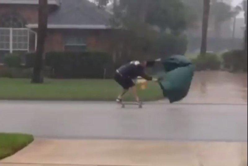 Billy Fortier uses a tarp to propel his skateboard down a Florida road during Hurricane Matthew. Screenshot: billyinhawaii/Instagram