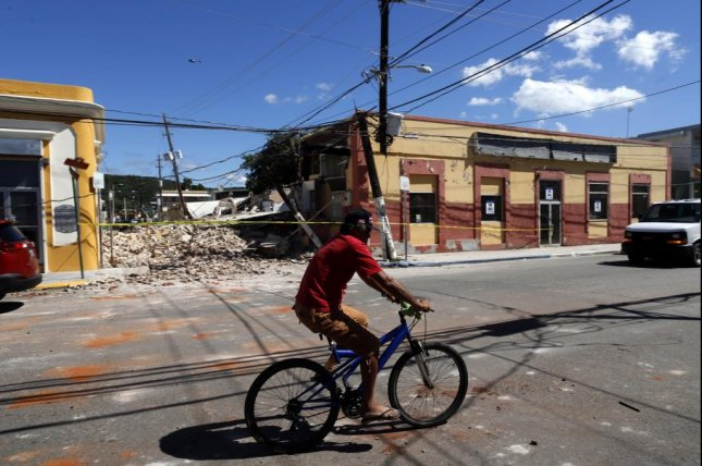 A bicyclist passes houses buckled by a magnitude-6.4 earthquake that shook Guayanilla, Puerto Rico, on Tuesday. Photo by Thais Llorca/EPA-EFE