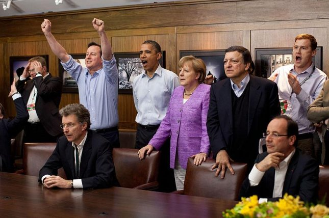 The G8, in happier times. Prime Minister David Cameron of the United Kingdom, President Barack Obama, Chancellor Angela Merkel of Germany, José Manuel Barroso, President of the European Commission, President François Hollande of France and others watch the overtime shootout of the Chelsea vs. Bayern Munich Champions League final, in the Laurel Cabin conference room during the G8 Summit at Camp David, Md., May 19, 2012. (Official White House Photo/Pete Souza)