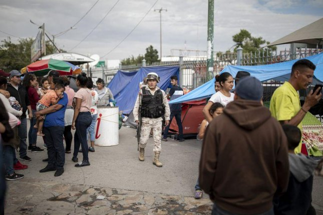 A Mexican soldier patrols a makeshift migrant camp at the base of Paso del Norte International Bridge in Ciudad Juárez, Mexico. Migrants wait close to the port of entry so they don't lose their spots in line to legally cross into the United States and seek asylum. Photo by Ivan Pierre Aguirre for The Texas Tribune