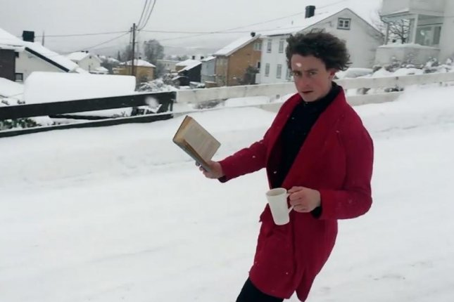 Norwegian snowboarder Trym Nordgaard enjoyed a book and some easy morning coffee while snowboarding down a residential street in a red house robe in a viral video. Photo by Trym Nordgaard/Facebook