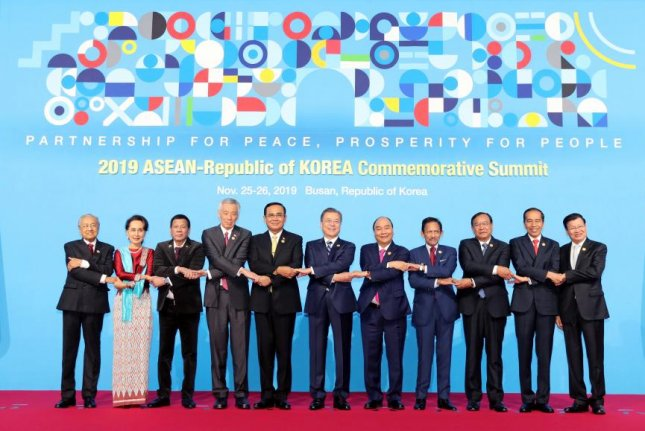 South Korean President Moon Jae-in (C) is flanked by other Asian leaders as they join hands for the traditional group photo during the during the ASEAN-South Korea Commemorative Summit in Busan, South Korea, on Tuesday. Photo by Yonhap/EPA-EFE