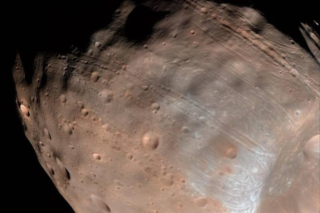 Researchers say stretch marks on Mars' moon Phobos are proof that it is slowly falling apart. Photo by NASA/Goddard