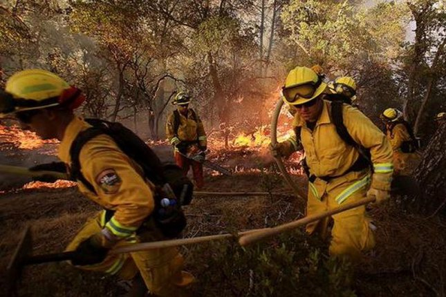 Firefighters work to battle the Rocky Fire in Napa Valley, Calif., on Thursday, July 30, 2015. The fire, fueled by wind gusts and dry vegetation, had burned nearly 20,000 acres and destroyed three structures by Friday evening. Photo: Cal Fire / Twitter