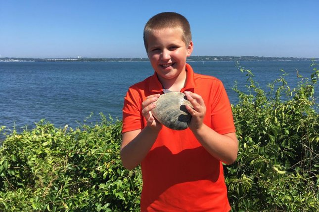 Cooper Monaco, 11, was out clamming with his grandfather when he discovered what scientists say might be the largest quahog ever found in Rhode Island waters. Photo courtesy ofTodd McLeish/University of Rhode Island's Marine Science Research Facility