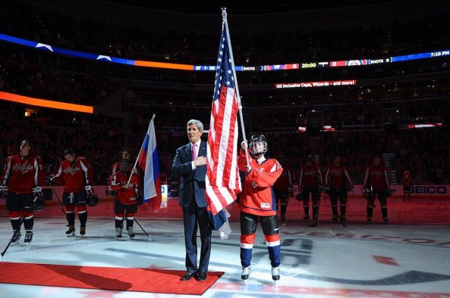 U.S. Secretary of State John Kerry sings the National Anthem at center ice at the Verizon Center in Washington, D.C., after honoring Olympics-bound hockey players before the Washington Capitals-Winnipeg Jets game on February 6, 2014. (CC/Flickr/State Department)