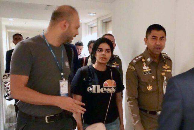Rahaf Mohammed Al-qunun (C) walks with Thai Immigration Police Chief Surachet Hakparn (R) at a transit hotel inside Suvarnabhumi International Airport in Bangkok, Thailand, Monday. Photo by Thai Immigration Bureau/EPA-EFE