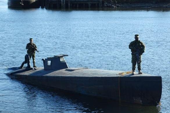 Colombian police stand aboard a submarine they say was ready to be used by drug smugglers to bring cocaine to the United States. Police made a second such discovery two days later. Photo courtesy Colombian government