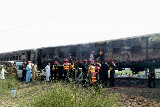Rescue workers search for bodies Thursday after a fire engulfed a passenger train near Rahim Yar Khan, Pakistan. Photo by EPA-EFE