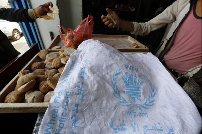 A man displays bread covered with a sack of the World Food Program in Sanaa, Yemen, on Thursday. Photo by Yahya Arhab/EPA-EFE