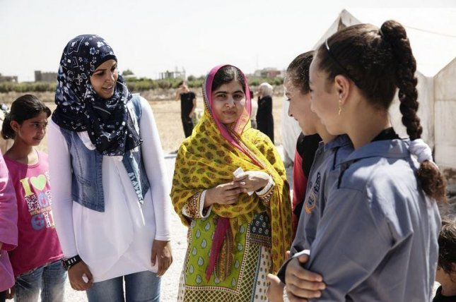 Nobel Prize laureate Malala Yousafzai (center) speaks with young female Syrian refugees at the opening of a new school in Lebanon, Sunday, July 12, 2015. Malala, who was named one of the world's 100 most influential people by Time magazine in 2013, urged world leaders to use books, not bullets. Photo: The Malala Fund