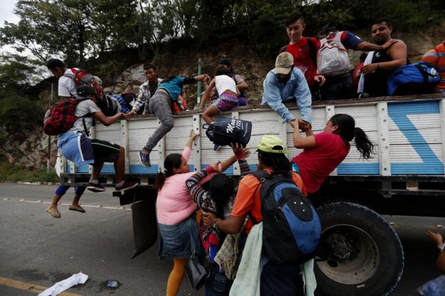 Honduran immigrants of the caravan heading to Mexico get on trucks to Guatemala City, in Zacapa, Guatemala, on Wednesday. Photo by Esteban Biba/EPA-EFE