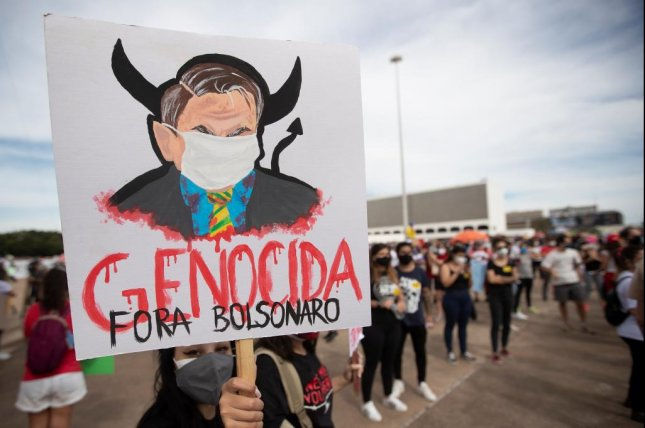 A protester holds a placard during protest against hisBrazilian President Jair Bolsonaro's government during a demonstration in Brasilia, Brazil Saturday. Photo by Joédson Alves/EPA-EFE