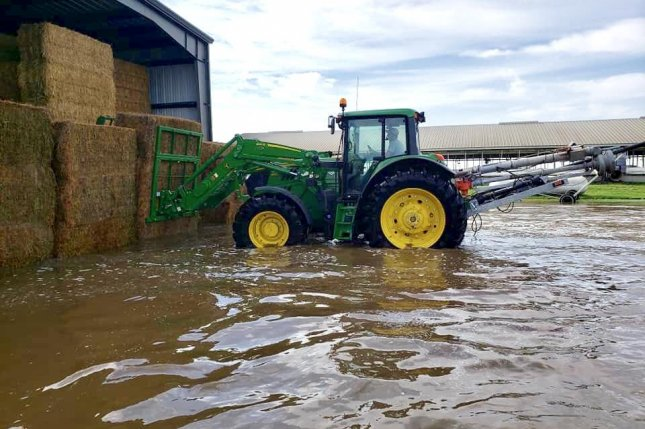 A farmer attempts to save his hay from rising water in South Dakota on Sunday. Photo courtesy of Jim Petrik