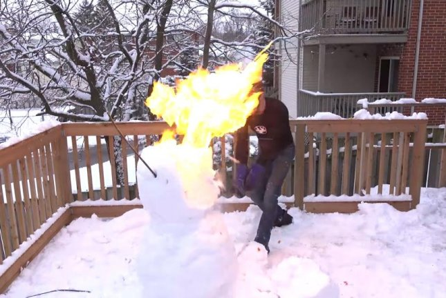 A snowman bursts into flames when sliced with a red-hot katana sword. Screenshot: The Hacksmith/YouTube