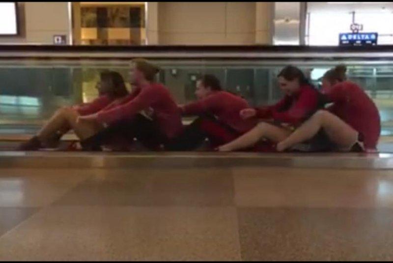 The University of Louisville Women's Swim and Dive Team practice their rowing skills on Raleigh-Durham International Airport's moving walkway. Kelsi Worrell/Facebook video screenshot