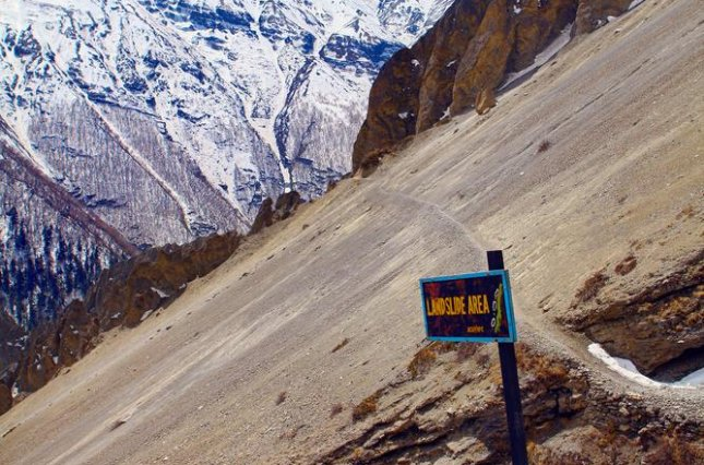 A landslide warning sign is posted high in the Himalaya Mountains in Nepal, where heavy rains can trigger dangerous landslides during the summer monsoon months. Photo: Vitaliy Mateha / Shutterstock