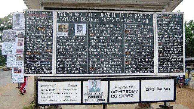 A daily news chalkboard in Monrovia, Liberia, follows the trial of former president Charles Taylor, who was later convicted of war crimes and crimes against humanity for his part in the Sierra Leone civil war, and sentenced to 50 years in prison. (PD/US Army)