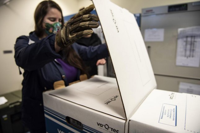 U.S. Air Force Staff Sgt. Anna Murray opens the first box of COVID-19 vaccinations delivered to Royal Air Force Lakenheath, England, on Sunday. Photo byJessi Monte/U.S. Air Force