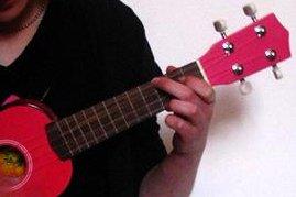 Someone playing a pink ukulele (CC/Dani Lurie)