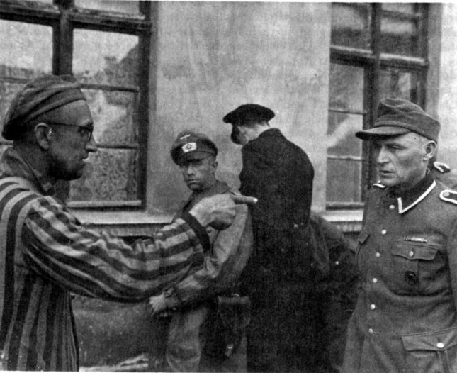 A Russian survivor of Buchenwald concentration camp in Germany, liberated by the U.S. Army, identifies a former guard who was brutally beating prisoners. Photo by Department of Defense