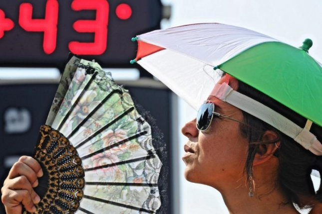 A woman in Florence, Italy, cools off as a thermometer reads 43 degrees Celsius -- 109 degrees Fahrenheit. High temperatures in an already hot summer are expected for Europe this week, meteorologists said Wednesday. Photo by Maurizio Degl'Innocenti/EPA
