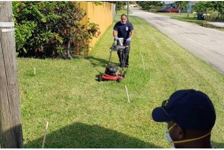 A firefighter finishes mowing the lawn of Prince Pinkney, 83, who suffered heat exhaustion and received treatment from rescuers. Photo courtesy of Fort Lauderdale Fire Rescue/Facebook