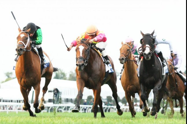 Grand Arch (center, orange and pink colors) holds off The Pizza Man (green colors) in the Grade I Shadwell Turf Mile at Keeneland Saturday 03 October. (Keeneland photo)