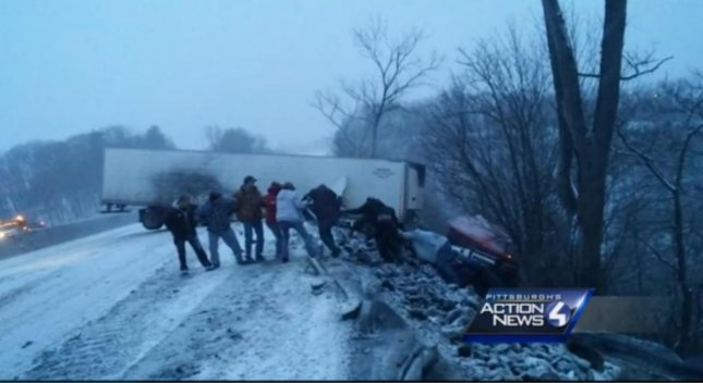 Strangers form a human chain to rescue a trucker whose vehicle was teetering on the edge of a cliff on the Pennsylvania Turnpike. Screenshot: WTAE-TV