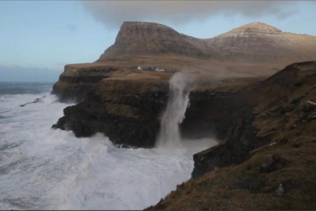 A waterfall in the Faroe Islands appears to flow upward amid extreme winds and high waves Dec. 5. Storyful video screenshot