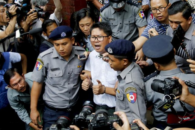 Reuters journalist Wa Lone (C) is escorted out of court in Yangon, Myanmar, on Monday. He and Kyaw Soe Oo were sentenced to seven years prison after they were found guilty of violating a state secrets. Photo by Lynn Bo Bo/EPA-EFE