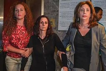Joy Morsi (center) is led out of a Queens courthouse by lawyer Virginia Lopreto (right) and bail bondswoman Michelle Esquenazi.