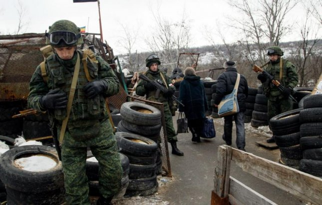 Local residents pass a checkpoint of pro-Russian rebels in eastern Ukraine on January 25. A Ukrainian military spokesman said Monday that five soldiers were killed in fighting on Sunday. Two others died Friday. Photo by Alexander Ermochenko/EPA