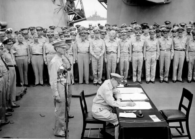 General Douglas MacArthur signs as Supreme Allied Commander during formal surrender ceremonies on the USS MISSOURI in Tokyo Bay on September 2, 1045. Behind General MacArthur are Lieutenant General Jonathan Wainwright and Lieutenant General A. E. Percival. Photo courtesy of United States Navy