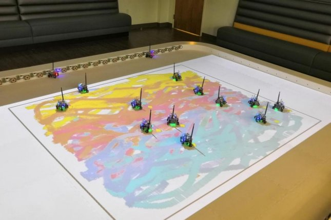 Researchers designed a swarm of bots to strategically apply paint to a canvas under direction from an artist. Photo by Maria Santos/Georgia Tech