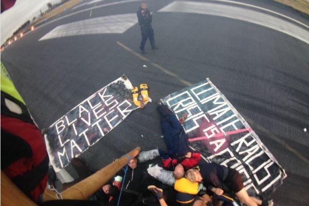 Nine Black Lives Matter UK activists chained themselves together with a wooden tripod on a runway at London City Airport on Tuesday. Photo courtesy Black Lives Matter UK/Twitter
