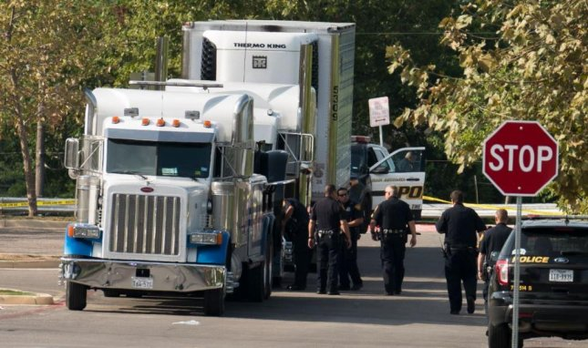 San Antonio, Texas, officials tow away a truck on Sunday, used to carry undocumented immigrants. Eight were found dead in the trailer, and two more people died later. Photo by Darren Abate/EPA